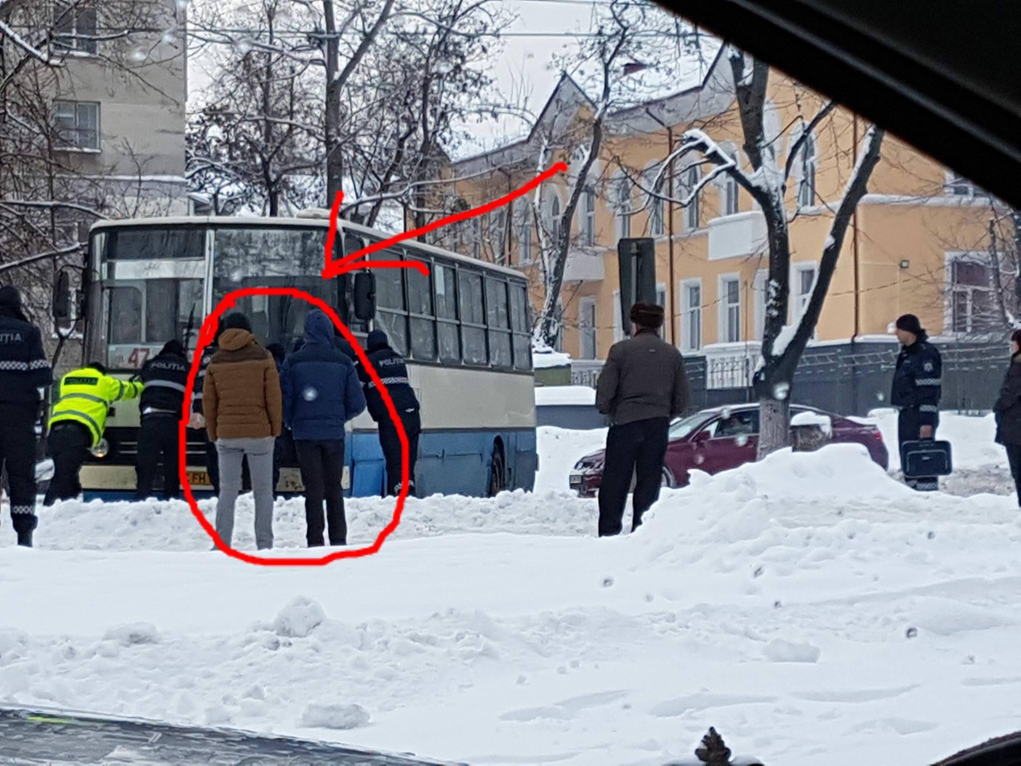 orasul chisinau, doi tineri s-au oprit și privesc cum mai mulți polițiști ajută un autocar blocat în zăpadă